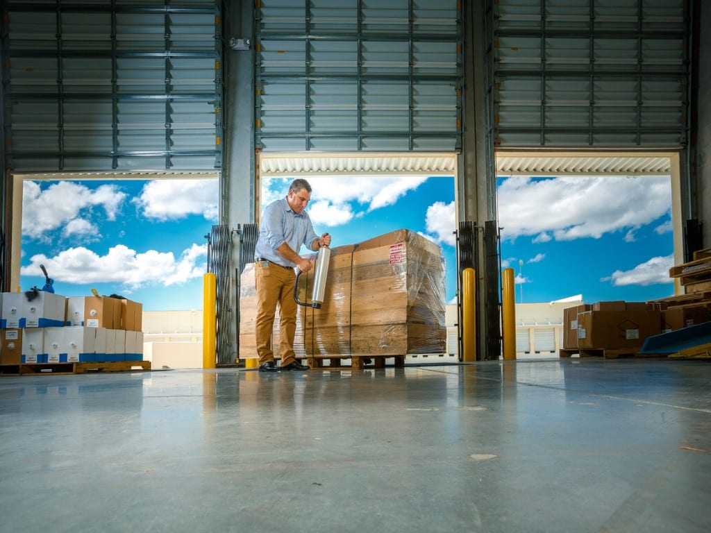 warehouse-manager-wrapping-merchandise-picture-id187068715